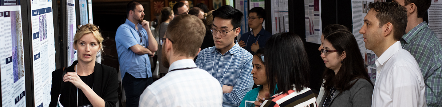 A student talking to a group of people while looking at a research poster