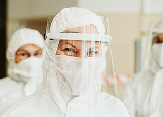 A woman in protective gear and a face shield